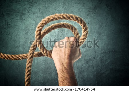 Male hand holding rope for salvation against grunge background. - stock photo