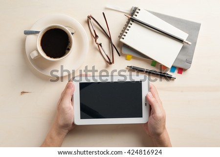 Male hand holding small tablet pc with notebooks, pen, and coffee cup beside on wood table in morning time