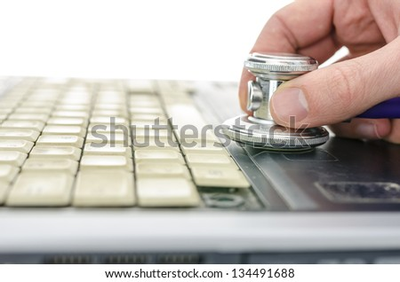 Male hand holding stethoscope on keyboard of an old and dirty laptop. Shallow dof. - stock photo
