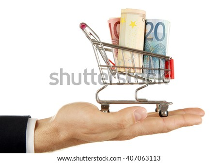 Male hand holding supermarket trolley with euro banknotes, isolated on white
