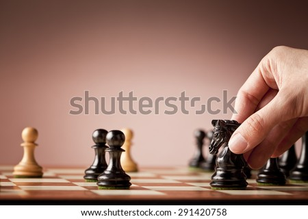 Male hand holding the black chess knight in focus at the end of a chess game