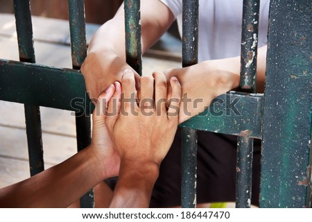 Male hand holding the hand of his brother, who was incarcerated in the prison bars of green. - stock photo