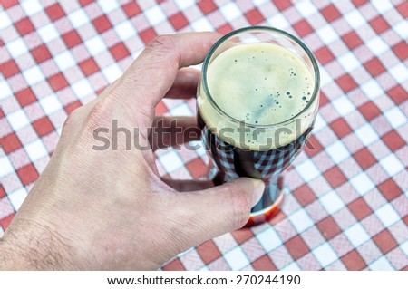 Male hand holding up a glass of dark beer on a vintage tablecloth - stock photo