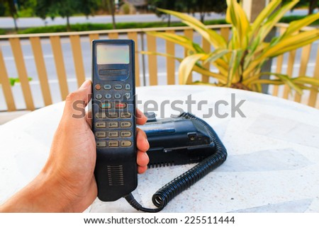 male hand holding vintage phone on white desk - stock photo