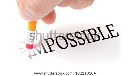 "Male hand holding wooden pencil and erase letters ""IM"" from word ""IMPOSSIBLE"" - stock photo"