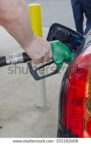 Male hand holds a pump nozzle filling up car with petrol at a petrol station. Car tail light and petrol filling door on image. Car is dark blue and petrol nozzle is green. Vertical portrait image.