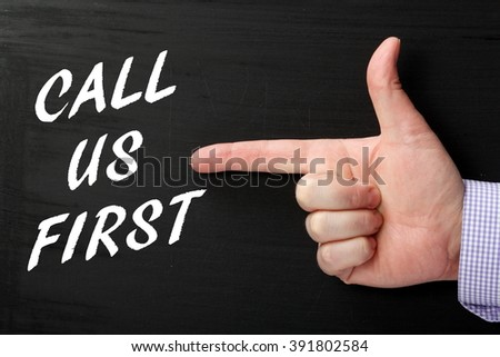 Male hand in a business shirt pointing a finger at the words Call Us First in white text on a blackboard