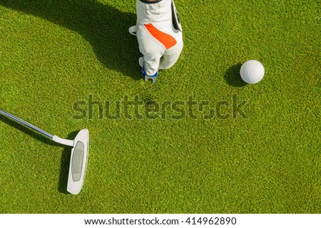 Male hand in glove marking ball position on the green. Focus on  pitchmark - stock photo
