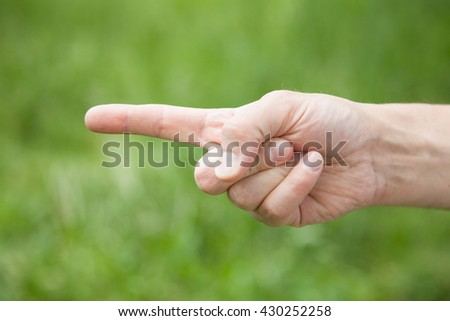Male hand indicating forward, natural green background