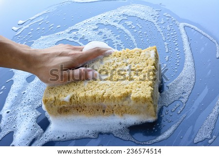 male hand is cleaning  car bonnet with yellow sponge ; selective focus at hand - stock photo