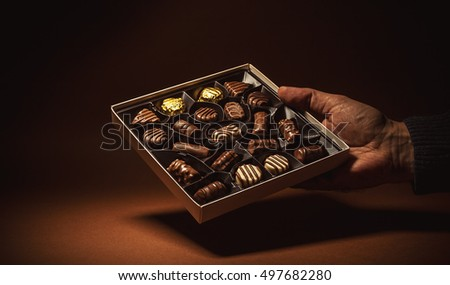 Male hand is holding an open box of chocolates.