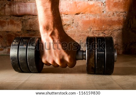 male hand is holding metal barbell against brick wall - stock photo