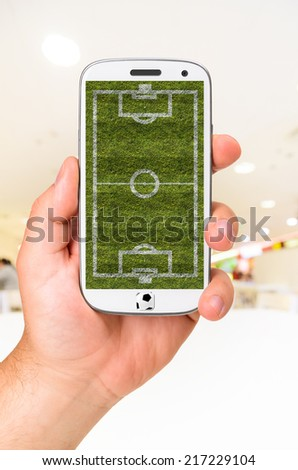 male hand is holding modern phone with soccer or football field on screen against blurred interior - stock photo