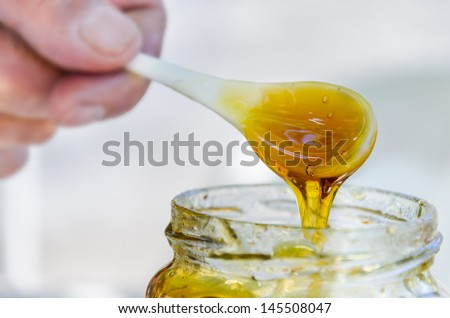 male hand is pouring honey from porcelain spoon drizzler into the jar, close up