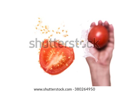 male hand is throwing a tomato against a pane, below shot - stock photo