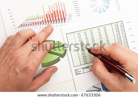 Male hand is writing in business document lying on the table - stock photo