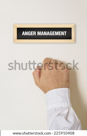 Male hand knocking on the door of Anger Management practice. - stock photo