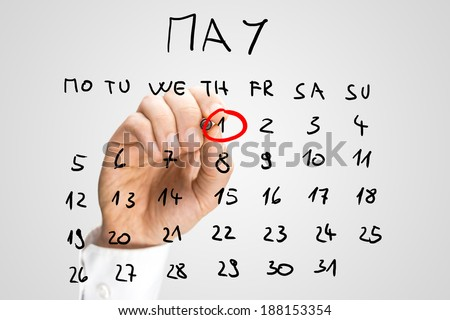 Male hand marking on a monthly calendar, placed on a virtual screen, the date of May 1,  International Workers Day, Labour Day or May Day. - stock photo
