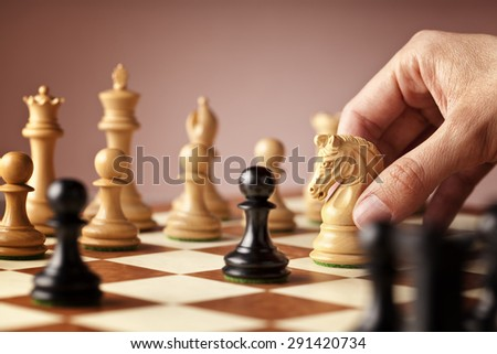 Male hand moving the white chess knight in the middle of a chess game attacking the blacks - stock photo