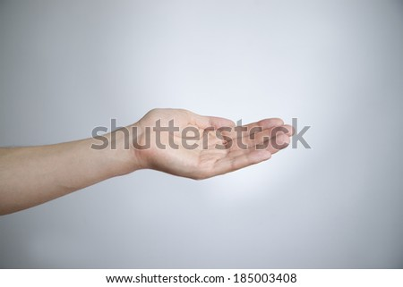 Male hand on a gray background. Empty outstretched palm. Copy space - stock photo