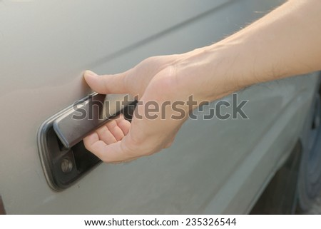 Male hand opening car door from outside by pulling black plastic door handle