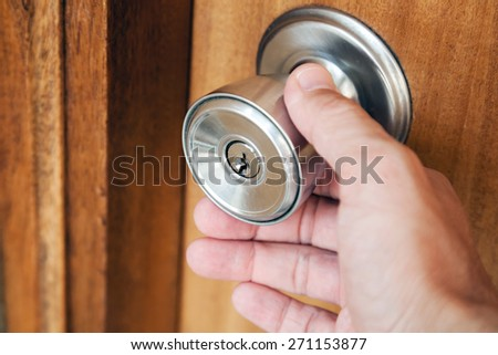 Male hand opening shining metal door handle in closed wooden door, photo with selective focus and shallow DOF