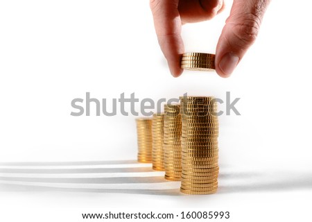 Male hand picking Euro Coins piled in stacks isolated on white background
