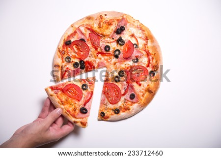 Male hand picking tasty pizza slice, studio shot on white background   - stock photo