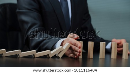 male hand placing wooden block on a tower. planing and strategy concept.
