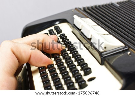 Male hand playing accordion - stock photo