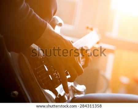 Male hand playing on acoustic guitar. Close-up. Sunflare - stock photo