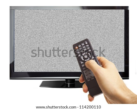 Male hand pointing remote control through TV screen with white noise isolated on white - stock photo