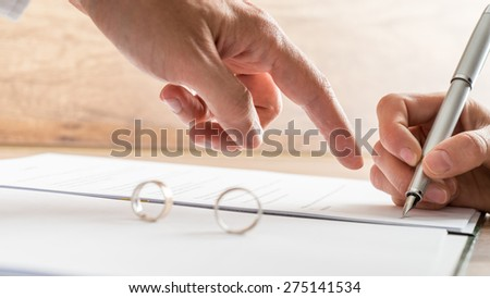 Male hand pointing to a divorce paper on which a woman is busy writing with a pen in a close up conceptual view. - stock photo