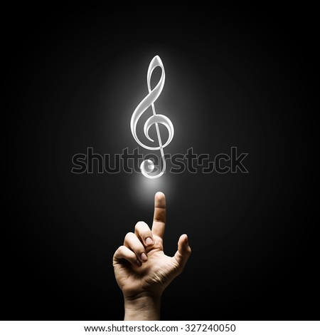 Male hand pointing with finger at music sign - stock photo