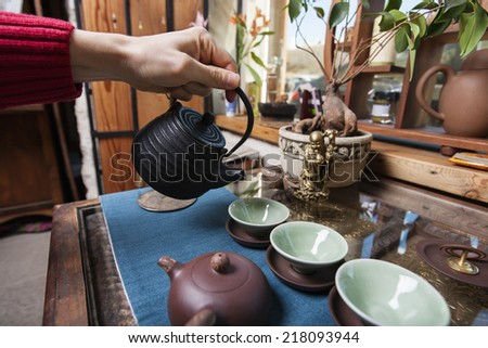 Male hand pouring tea into tea cups in store - stock photo