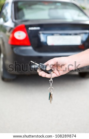 Male hand pressing on the remote control car alarm systems. Copyspace - stock photo