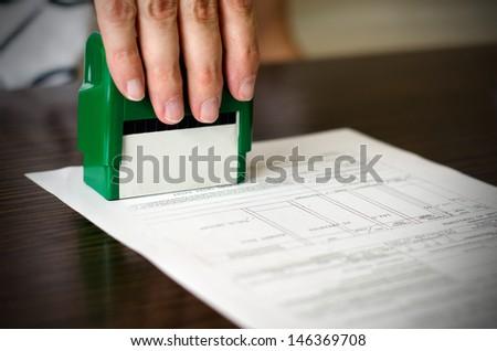 Male hand pressing rubber stamp on document. Dark desktop underneath - stock photo