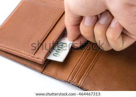 Male hand pulling money out of brown leather wallet on white background
