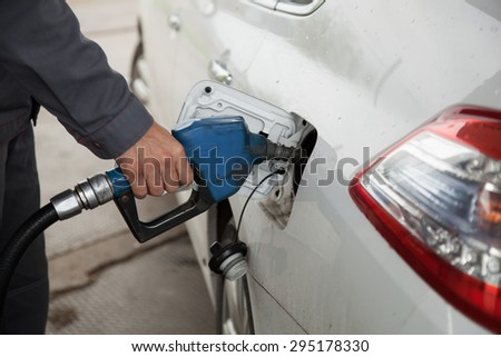Male hand pumping petrol into car, refueling with nozzle at gas station - stock photo