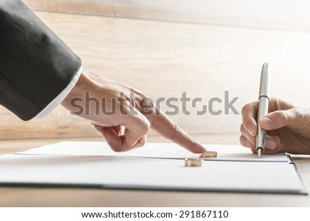 Male hand pushing a wedding ring over to a female hand about to sign  divorce papers. Conceptual of divorce or marriage. - stock photo