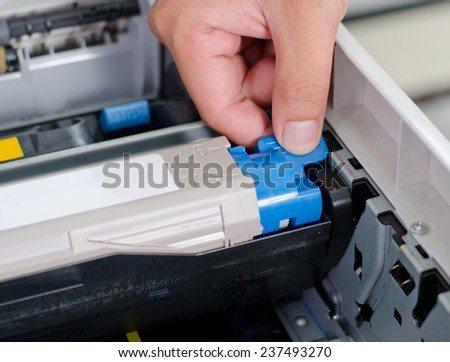 Male hand putting and lock color printer toner - stock photo