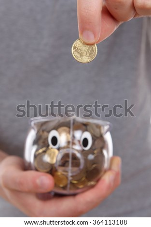 Male hand putting coin into a piggy bank. focus specifically on the coin. - stock photo