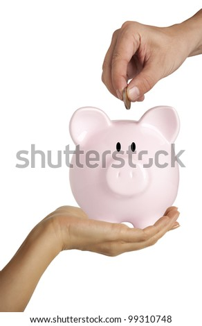 Male hand putting coin into a piggy bank isolated on white - stock photo