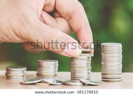 Male hand putting money coin like stack growing business - finance and money concept