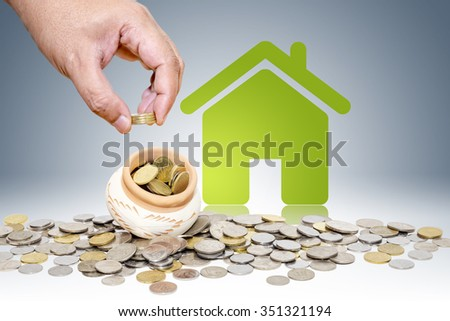 Male hand putting money coins with green home, Saving for buy home concept - stock photo