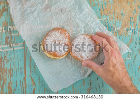 Male hand reaches and picking sweet sugary donut from rustic wooden kitchen table, tasty bakery doughnuts overhead shot, top view - stock photo