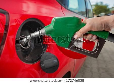 Male hand refilling automobile fuel - stock photo