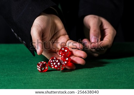 Male hand rolling five dice on green felt