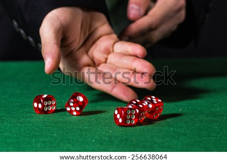 Male hand rolling five dice on green felt - stock photo