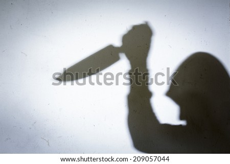 Male Hand Shadow with Kitchen Knife, on concrete wall - stock photo